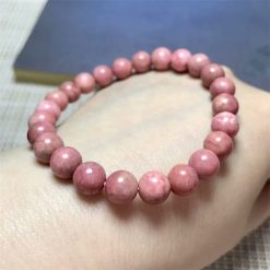 bracelet en pierre de rhodonite rose sur son support